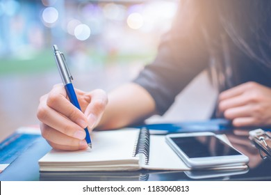 Woman hand writing on a notebookwith a pen.On the table with a smartphone