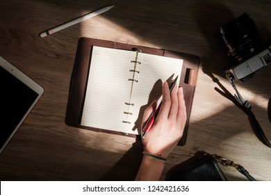 Woman hand writing  on notebook diary with vintage camera and tablet computer on wooden desk in morning sunlight,Top view work desk concept.