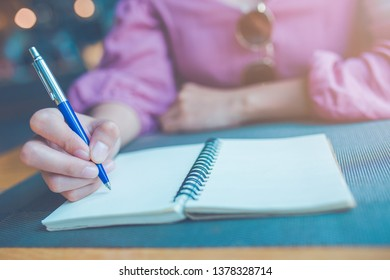 Woman hand is writing on a notebook with a pen.