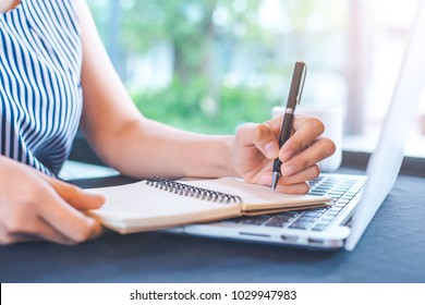Woman hand writing on notepad with a pen in the office.
