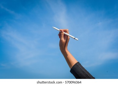 woman hand writing with pen on blue sky background