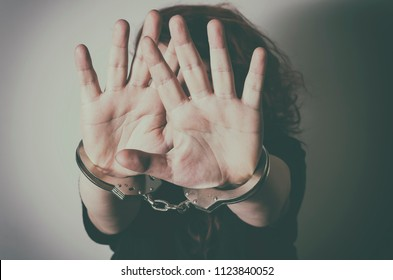 Woman with handcuffs hiding face with her hands