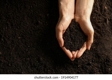 Woman with handful of soil outdoors, top view. Space for text