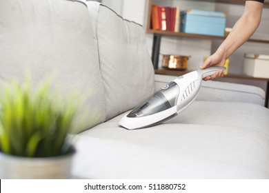 Woman with handheld vacuum cleaning on sofa