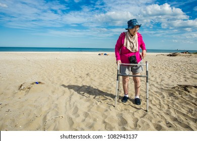 woman with handicap walking on sand at the beach