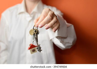 woman is handing a house key. Key with a key chain in the shape of house