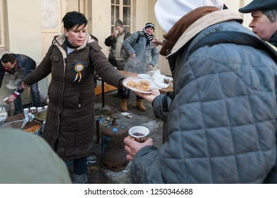 A woman is handing out a warm plate of cooked food to a poor man during an organized free lunch after the National Day parade was over. Bucharest, România,December 1,2018.