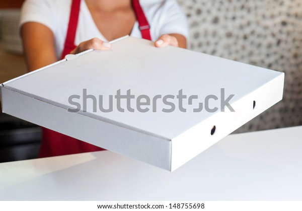 Woman handing over pizza, cropped image.