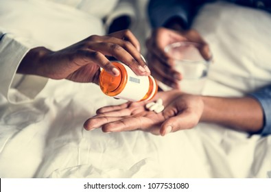 A woman handing pills to her boyfriend