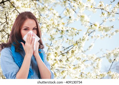 Woman with handkerchief and hay fever in front of a flowering tree