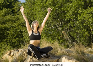 Woman with hands above head in praise in park