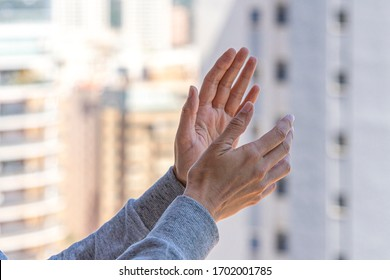 Woman hands applauding medical staff from balcony. People in Spain clapping gratitude on balconies and windows in support of health workers, doctors and nurses during the Coronavirus pandemic