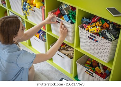 Woman hands applying printing sticker with name title of children toys for comfortable sorting and storage at home. Caring mother organizing domestic space for kids. Housekeeping and household