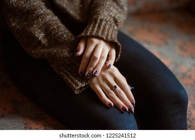 Woman hands with beautiful manicure. in the living room