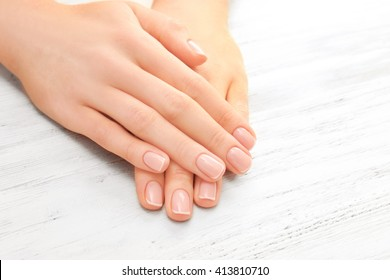 Woman hands with beautiful manicure on wooden background