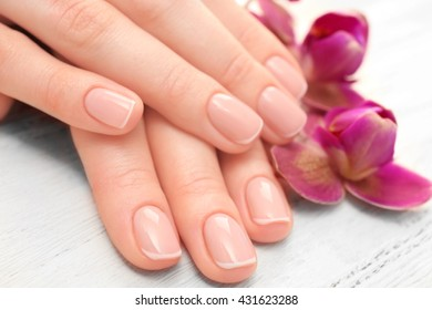 Woman hands with beautiful manicure and purple orchid on wooden background, close up