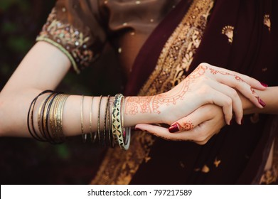 Woman Hands with black mehndi tattoo. Hands of Indian bride girl with black henna tattoos. Fashion. India