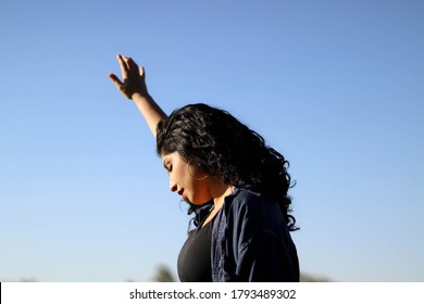 woman with hands up to blue sky