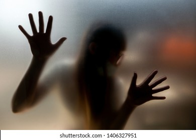 The woman hands and body at the back of frosted glass in the building to present the scary feeling.