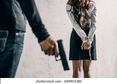 woman hands bound and man holding a gun. Women were handcuffed.woman tied hand.Crime Concept.Criminality Concept.