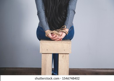 woman hands bound on the dark wall background