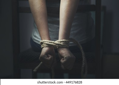 woman hands bound prisoner in room