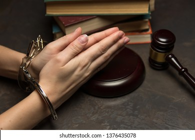 woman hands in bracelets lie on dark background  beside judge gavel
