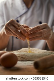 Woman hands breaking egg on pasta dough. Fresh ingredients. Meal preparation.