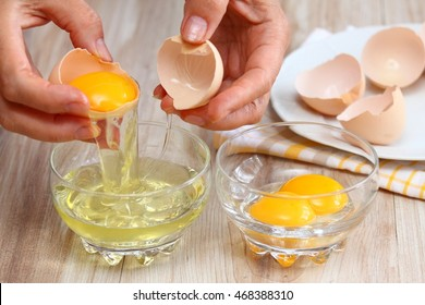 Woman hands breaking an egg to separate  egg white and  yolks and egg shells at the background