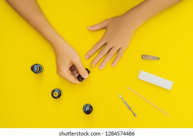 Woman Hands Care. Top View Of Beautiful Smooth Woman's Hands With Professional Nail Care Tools For Manicure On yellow Background. Closeup Of Healthy Female Nails With yellow Nail Polish. High