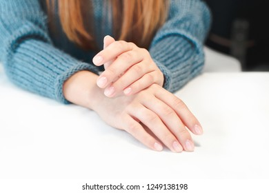 Woman hands with clean manicure and on white table close-up. Female client in a cozy blue sweater.
