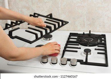 woman hands cleaning gas cooker in the kitchen