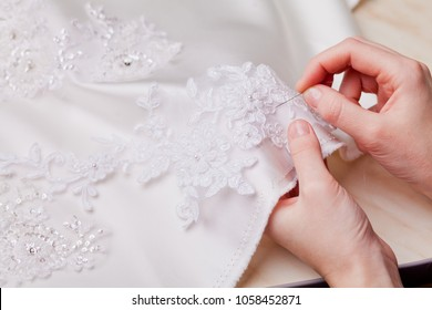 woman hands close up sewing a wedding dress, white material decorated with lace, tailoring clothes, white fabric
