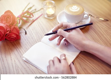 Woman hands close-up writing in notebook, using pencil, blank pages for layout. Cappuccino latte coffee with heart on top. Flowers on wooden table in modern cafe. St. Valentines celebration concept