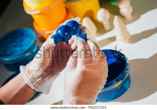 woman hands are coloring a wooden toy by blue color on the wooden cube. Eco toys for children. Close up