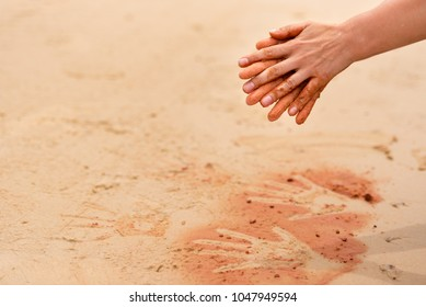 Woman hands creating shapes with red sand on the beach in aboriginal art style, template for creative projects