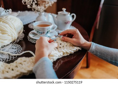 Woman hands crocheting on the table and drinking tea, using white wool crochet yarn, relax crafts hobby
