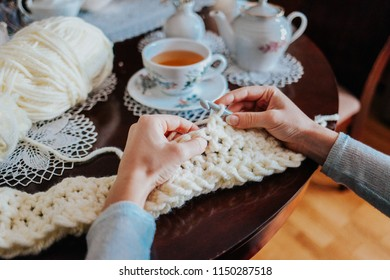 Woman hands crocheting with white wool yarn on the table, drinking herbal tea, handmade hobby crafts relax with lace tablecloth