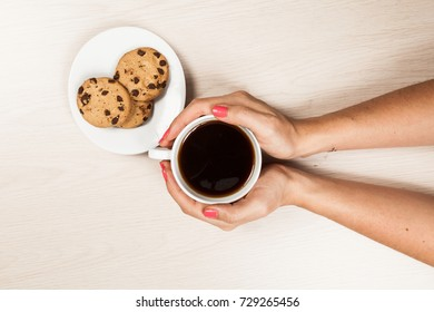 woman hands with cup of coffee with cookies