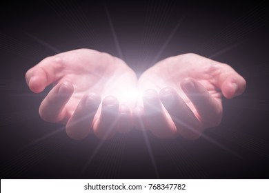 Woman hands cupped protecting and holding bright, glowing, radiant, shining light. Emitting rays or beams expanding. Religion, divine, heavenly, celestial concept. Black background, front view