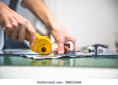 Woman hands cut fabric to smaller parts with rotary cutter. Quilting.