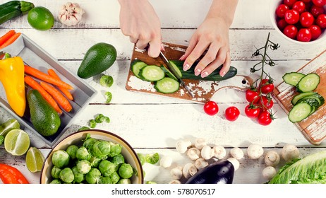 Woman hands cutting cucumber and organic vegetables on white wooden board. View from above