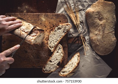 Woman hands cutting a loaf of bread on rustic wooden board and paper sheets, with wheat ears and knife, top view.