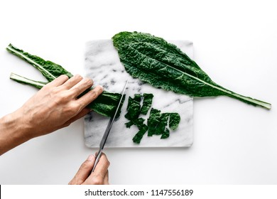 Woman hands cutting organic green kale leaves on a marble board over a white table background, healthy cooking nutrition concept, top view