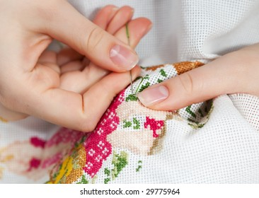 Woman hands doing cross-stitch. A close up of  embroidery.