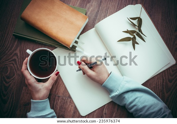 Woman hands drawing or writing, tea, pumpkin cake on wooden table. Toned picture