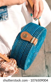 Woman hands with fashionable stylish blue rattan bag and silk scarf outside. Tropical island of Bali, Indonesia. Rattan handbag and silk scarf.