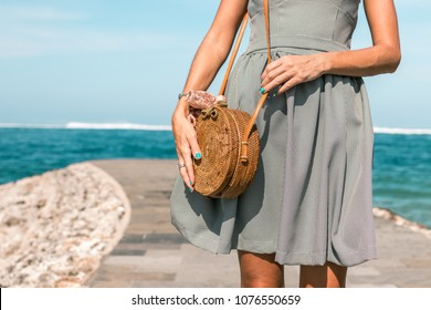 Woman hands with fashionable stylish nude rattan bag and silk scarf outside. Tropical island of Bali, Indonesia. Rattan handbag and silk scarf.