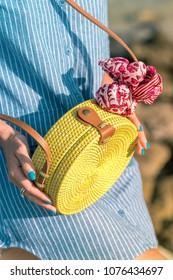 Woman hands with fashionable stylish rattan bag and silk scarf outside. Tropical island of Bali, Indonesia. Rattan handbag and silk scarf.