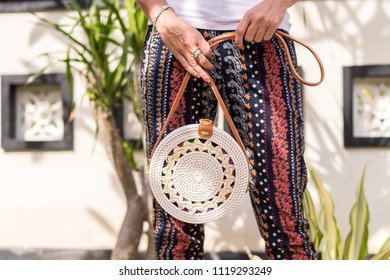 Woman hands with fashionable stylish white rattan bag. Tropical island of Bali, Indonesia. Rattan handbag.